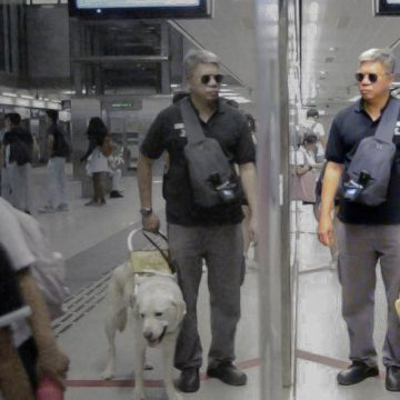 Mr Gary Lim and his guide dog Jordie waiting to enter a MRT cabin. Photo by: Jolynn Lee, Bibiana Inez Low