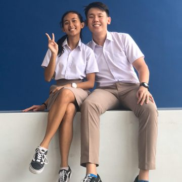19-year-olds Truman Lee and Corine Chong sitting on top of a wall and posing for the photo