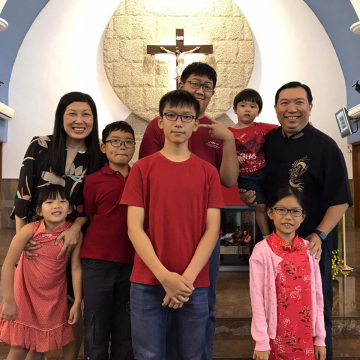Mr Kelvin Tan's family of 8 posing in front of a church altar