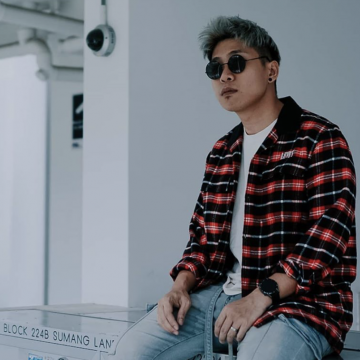 Johnathan Chua, host of the Youtube show Real Talk and owner of Grvty Media, sitting on top of mail boxes at a HDB void deck.